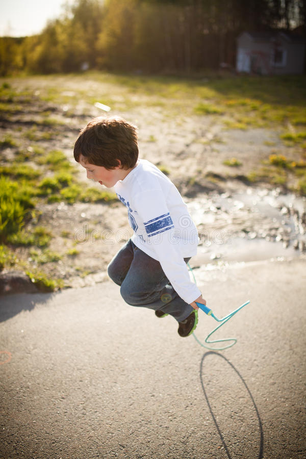 Boy playing jump rope. Cute little boy playing jump rope stock photos