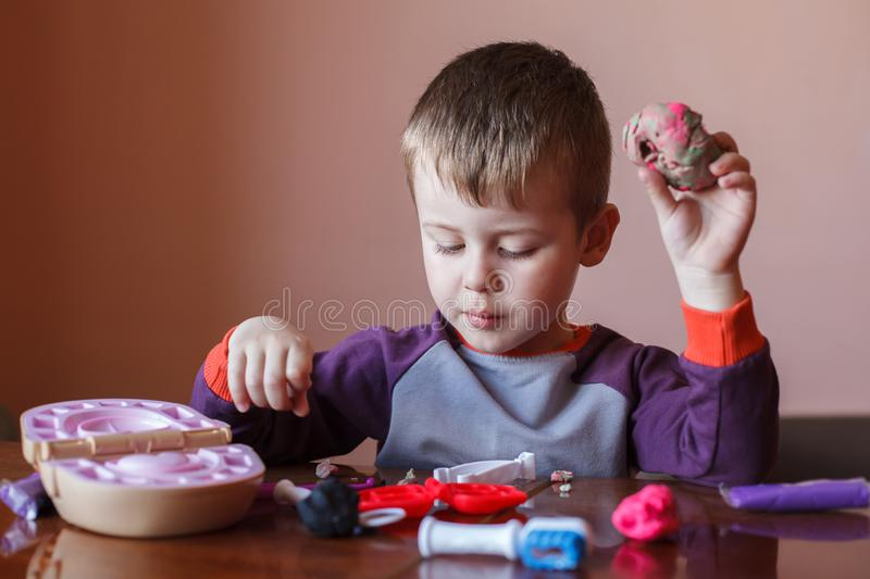 Cute little boy playing with many-colored plasticine. Boy playing with toys Dental Tools. Facial expression. Positive, negative royalty free stock image
