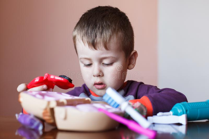 Cute little boy playing with many-colored plasticine. Boy playing with toys Dental Tools. Facial expression. Positive, negative stock photography