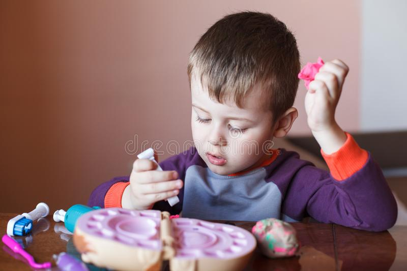 Cute little boy playing with many-colored plasticine. Boy playing with toys Dental Tools. Facial expression. Positive, negative royalty free stock photos