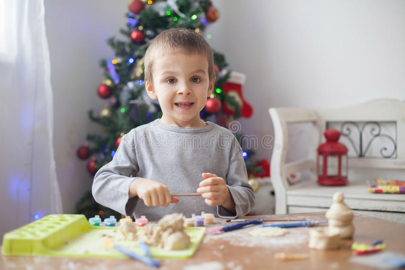 Cute little boy, playing with modeling dough, molding figures at home royalty free stock photos