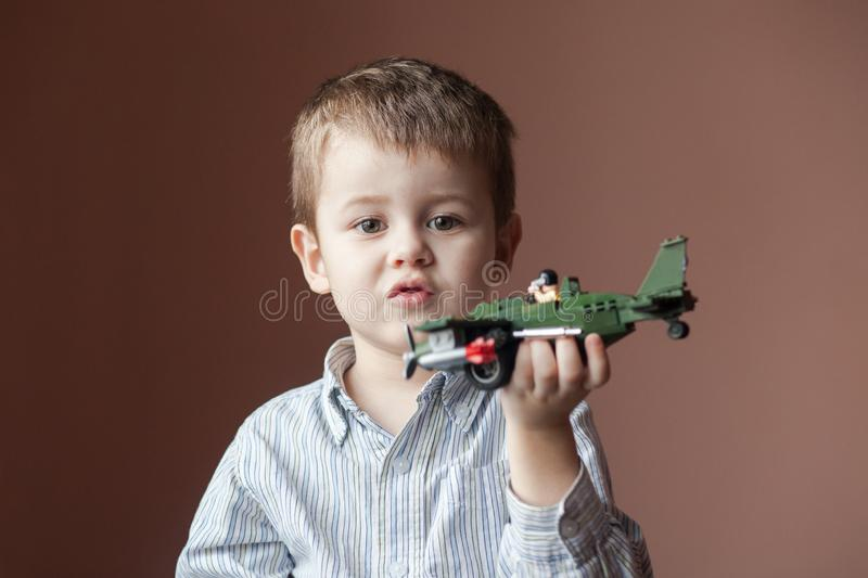 Cute little boy playing with a toy airplane. Military Aircraft LEGO royalty free stock photos