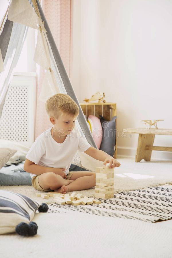 Cute little boy playing with wooden blocks in scandinavian playroom, real photo with copy space on empty wall royalty free stock photos