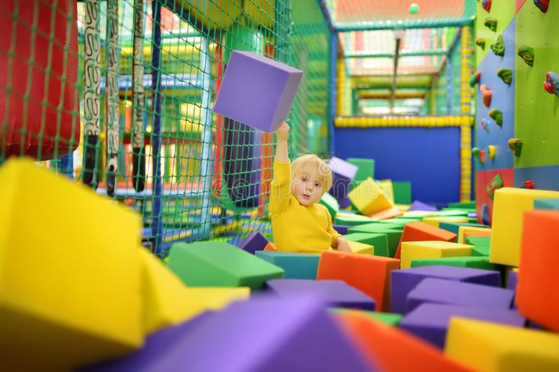 Cute little boy plays with soft cubes in the dry pool in play center. Kid playing on indoor playground in foam rubber pit in stock images