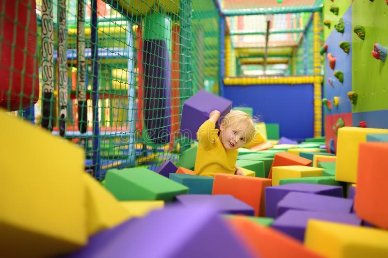 Cute little boy plays with soft cubes in the dry pool in play center. Kid playing on indoor playground in foam rubber pit in. Trampoline. Child having fun in royalty free stock photo
