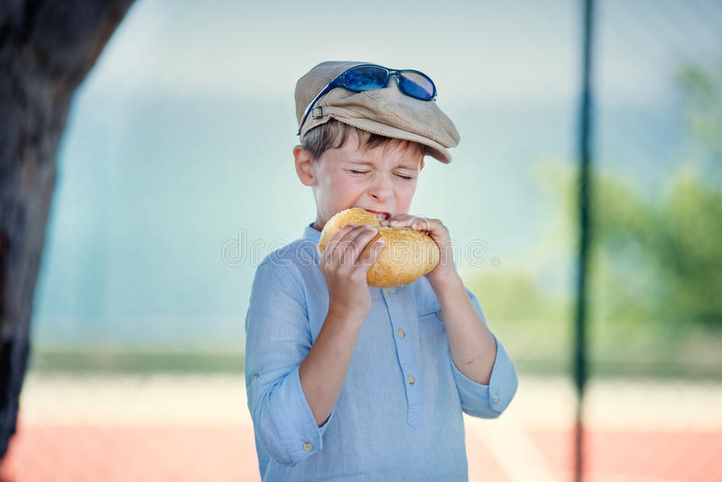 Cute little boy with pleasure eats hamburger royalty free stock photography
