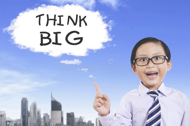 Cute little boy pointing at Think Big text stock image
