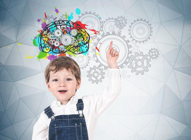 Cute little boy pointing up, gear brain. Adorable little boy in jeans overalls pointing up standing near gray wall with colorful brain sketch, cogs and gears royalty free stock photography