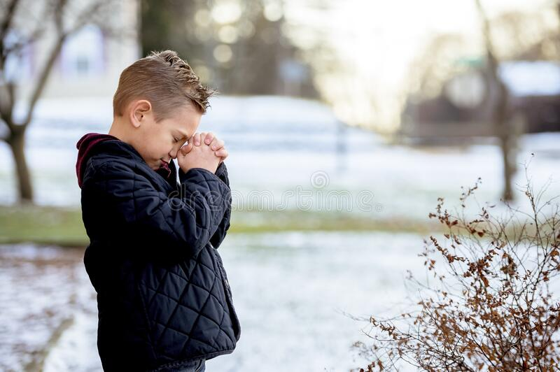 Cute little boy praying with closed eyes in the middle of the winter park royalty free stock image