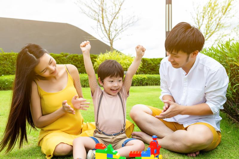 Cute little boy raise hands up and get happiness that kid can finish homework. Mother and father give son a big hand for stock photography
