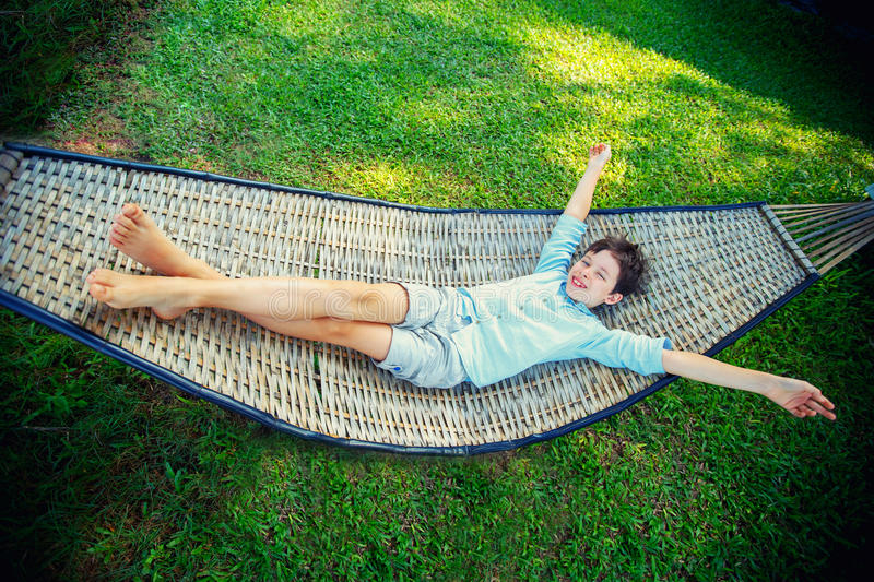 Cute little boy relaxing in a hammock during summer vacation stock photo