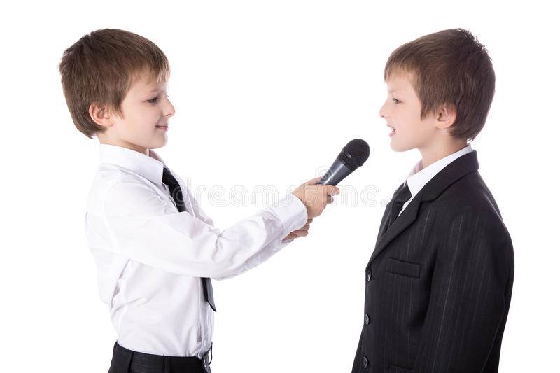 Cute little boy reporter with microphone taking interview isolated on white. Cute little boy reporter with microphone taking interview on white background stock photo