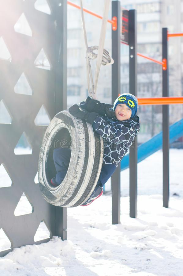 Cute little boy ride on a swing in winter. happy children having fun, playing at winter walk outdoors royalty free stock photography