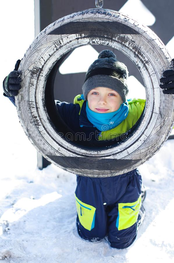 Cute little boy ride on a swing in winter. happy children having fun, playing at winter walk outdoors royalty free stock photos