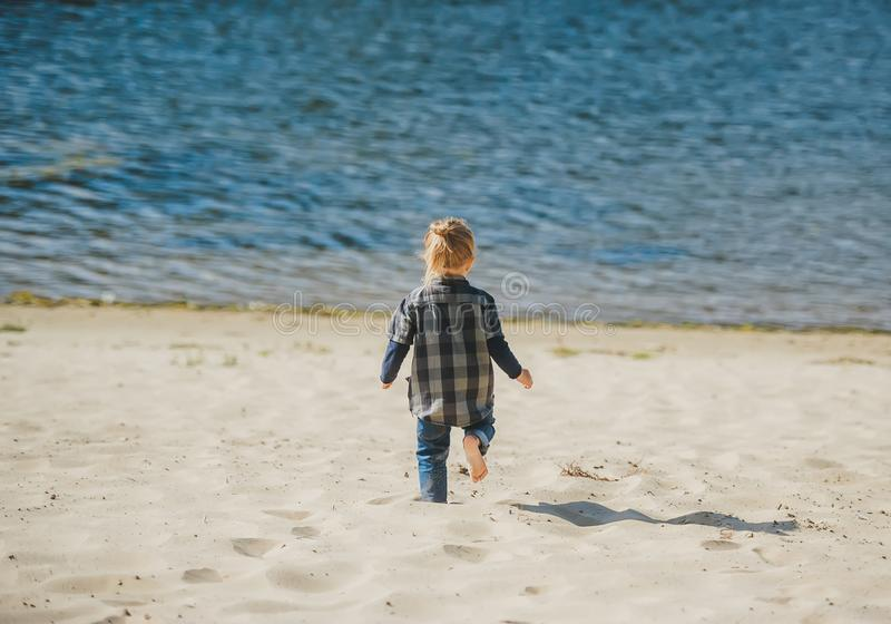 Cute little boy runing on sandy beach. Rear view stock photography