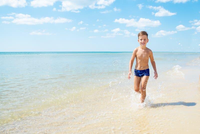 Cute little boy running through the water at beach stock image