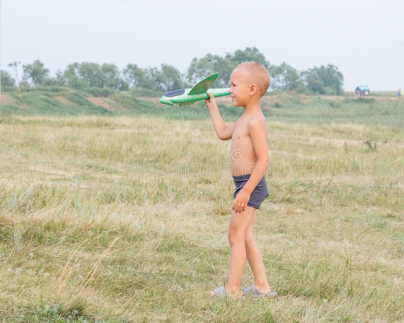 Cute little boy in shorts walks across the field and holds a toy airplane in his hand stock photo