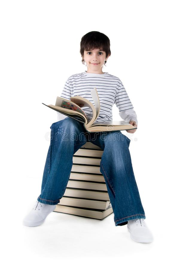Cute little boy sit on a stack of big books