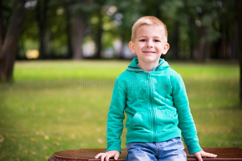 Cute little boy sitting on bench royalty free stock photos