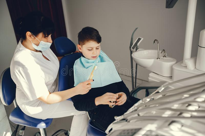 Cute little boy sitting in the dentist`s office. Little boy talking to the dendist. Child in the dentist`s office. Woman in a uniform royalty free stock photo