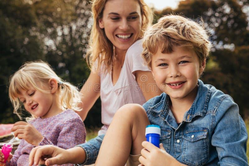 Family of three having picnic at park stock photo