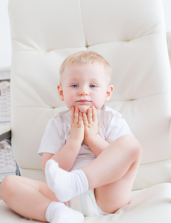 Cute little boy is sitting on the white chair royalty free stock image