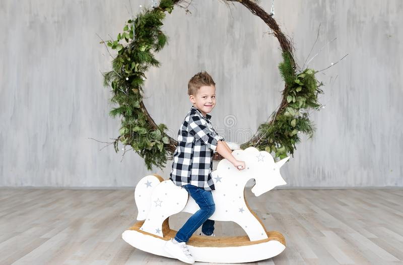 Cute little boy sitting on a wooden toy horse in an interior of studio stock photo