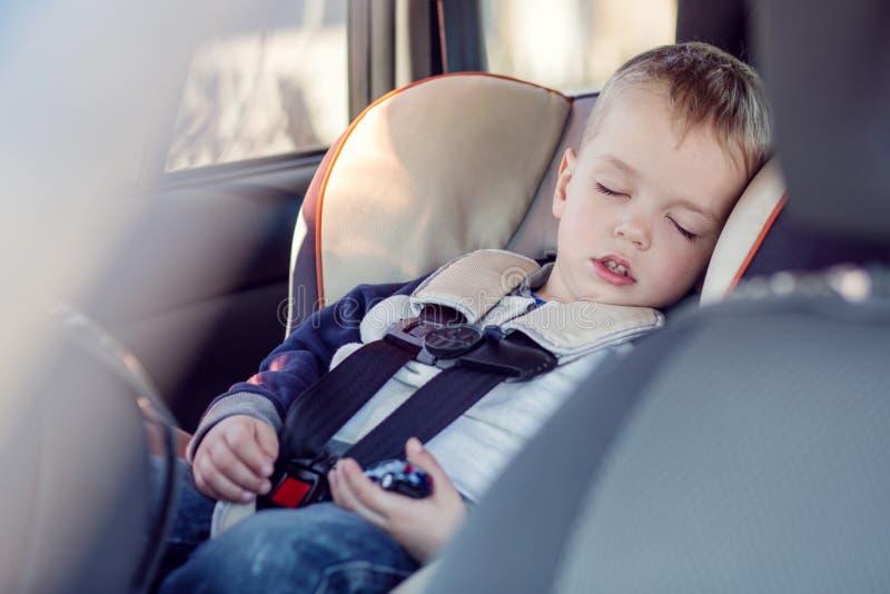 Cute little boy sleeping in car stock photo