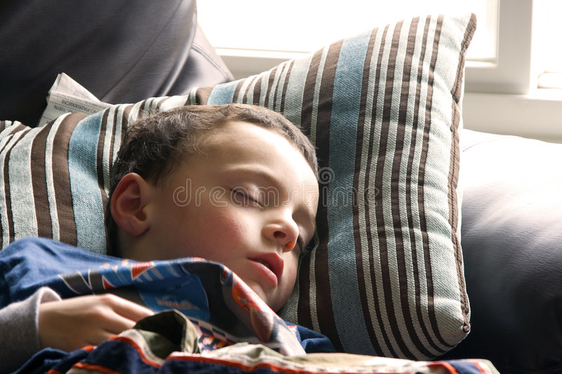 Cute Little Boy Sleeping on the Couch stock images