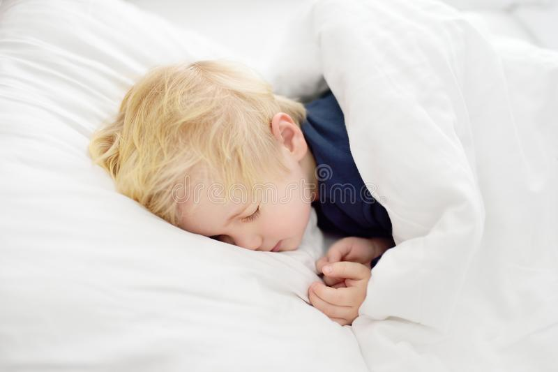 Cute little boy sleeping. Tired child taking a nap in parent`s bed. Clean, fresh and cozy bedding sheets. Bedtime for kids royalty free stock photos