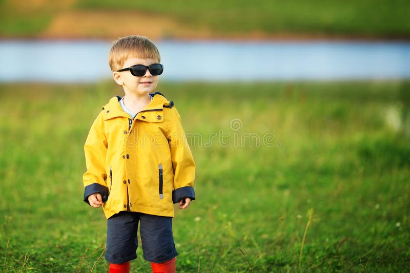 Cute little boy smiles in garden in sunglasses outdoors stock photo
