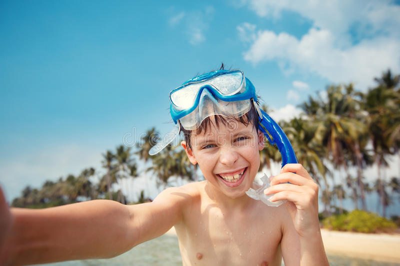 Cute little boy in snorkeling mask making selfie at tropical beach on exotic island stock image
