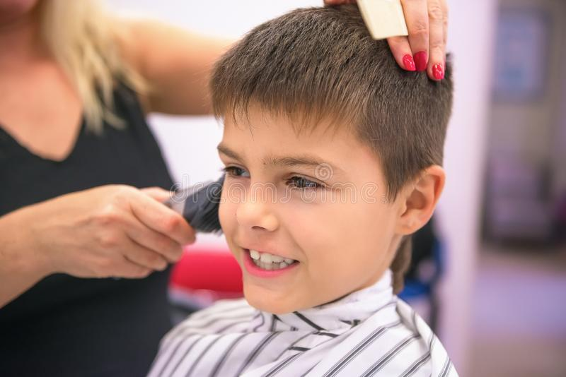 Cute little boy in stripped salon cape in barbershop. Woman barber with in black top does kid hairstyle. Portrait with selective royalty free stock photography