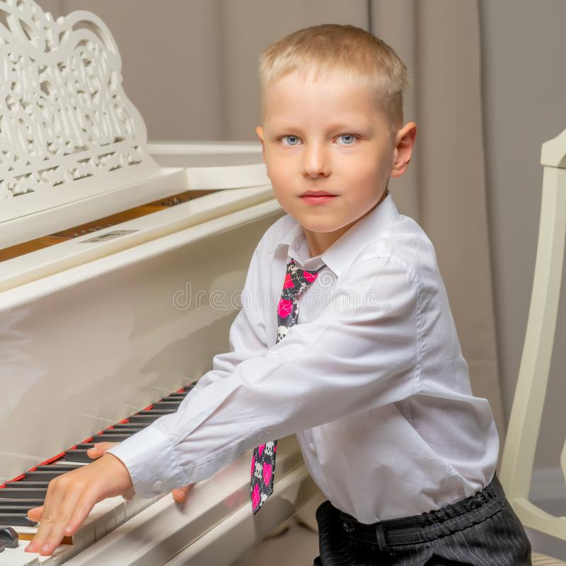 Little boy in studio near white piano. royalty free stock photos