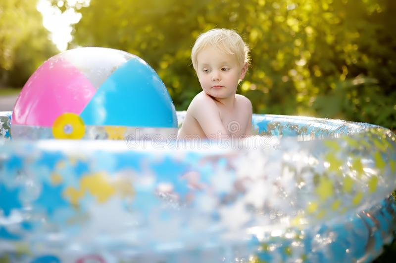 Cute little boy swimming in a inflatable pool outdoors on the backyard at sunny summer day. Cute little boy swimming in a inflatable pool outdoors on the royalty free stock images