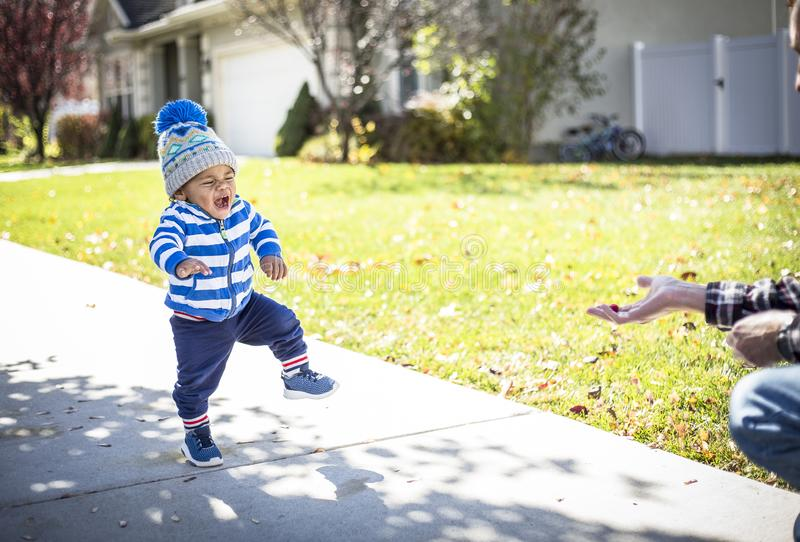 Cute little boy taking big steps as he makes a big effort to learn how to walk. A cute little Africa American little boy learning to walk and taking big steps stock image