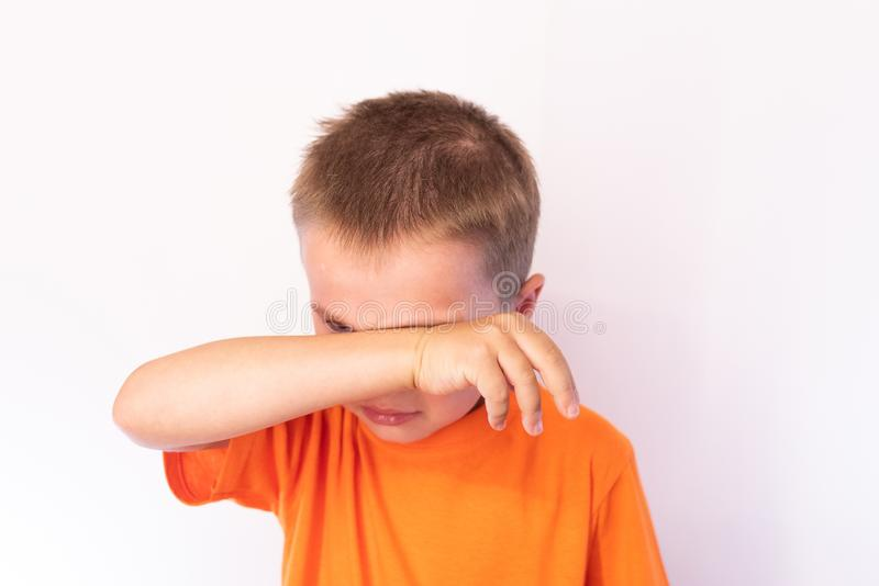 Cute little boy with tear-stained face and hand wipes his tears on a light background. For any purpose stock photography