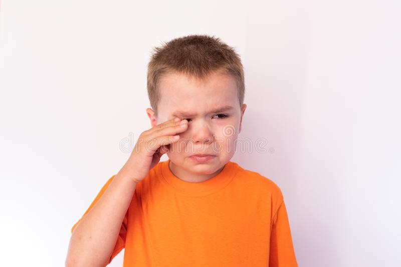 Cute little boy with tear-stained face and hand wipes his tears on a light background. For any purpose stock image
