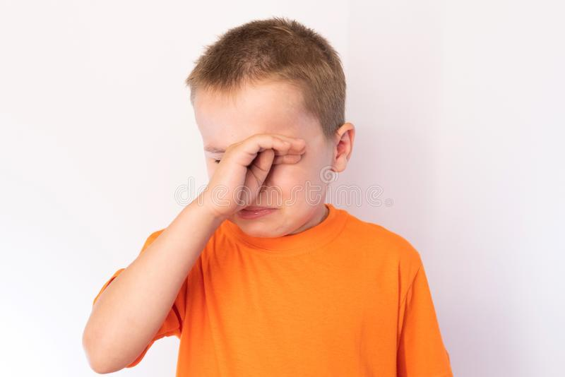 Cute little boy with tear-stained face and hand wipes his tears on a light background. For any purpose royalty free stock photos