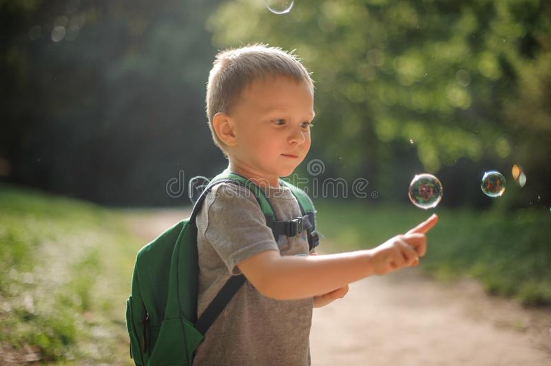 Cute little boy touching a soap bubble playing in the park royalty free stock photos
