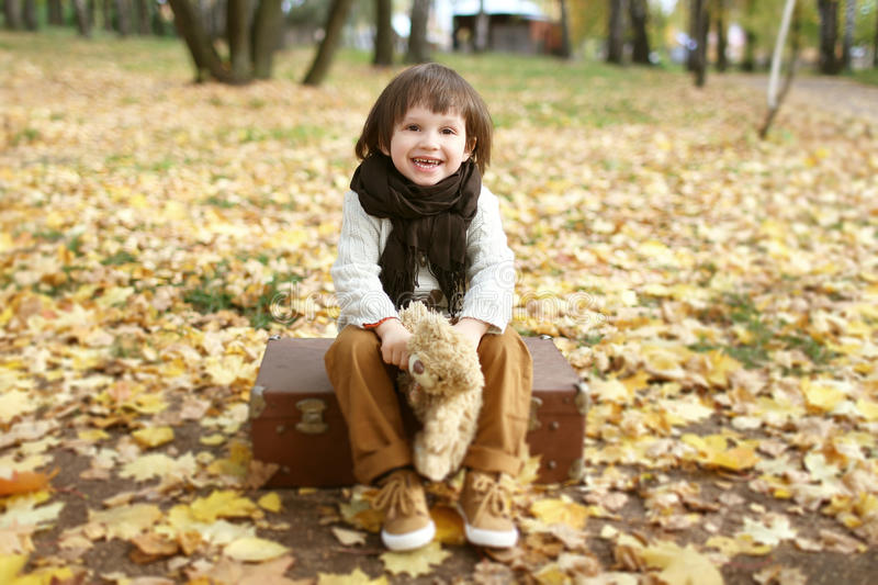 Cute little boy with toy bear sitting on suitcase in the autumn. Cute fashionably dressed boy with toy bear sitting on suitcase in the autumn park royalty free stock image