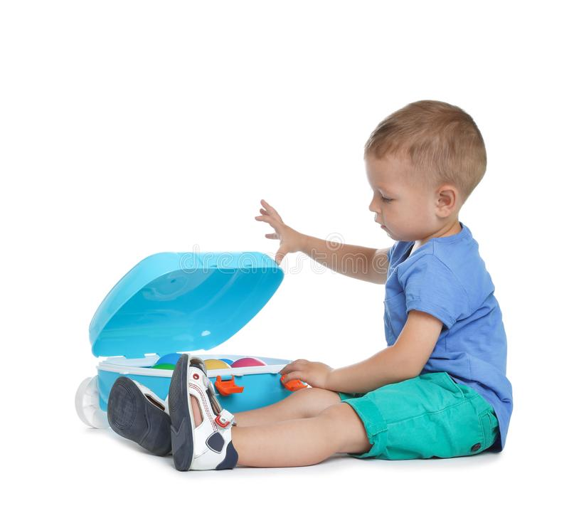 Cute little boy with toys and blue suitcase on white stock photo