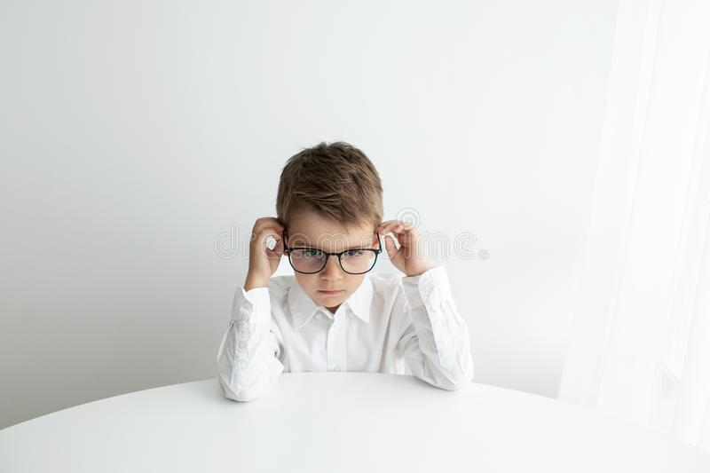 Cute little boy using laptop while doing homework against white background royalty free stock image