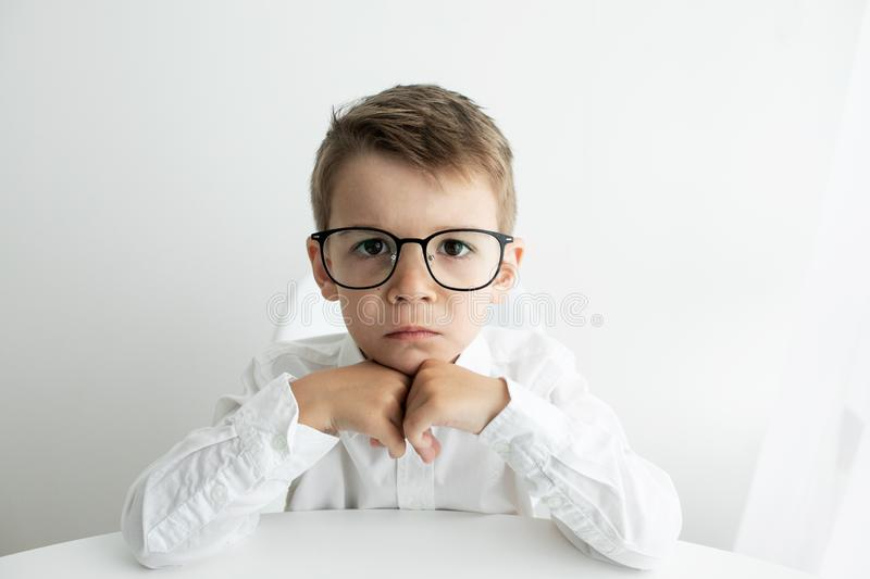 Cute little boy using laptop while doing homework against white background stock photos