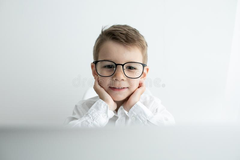 Cute little boy using laptop while doing homework against white background royalty free stock photo