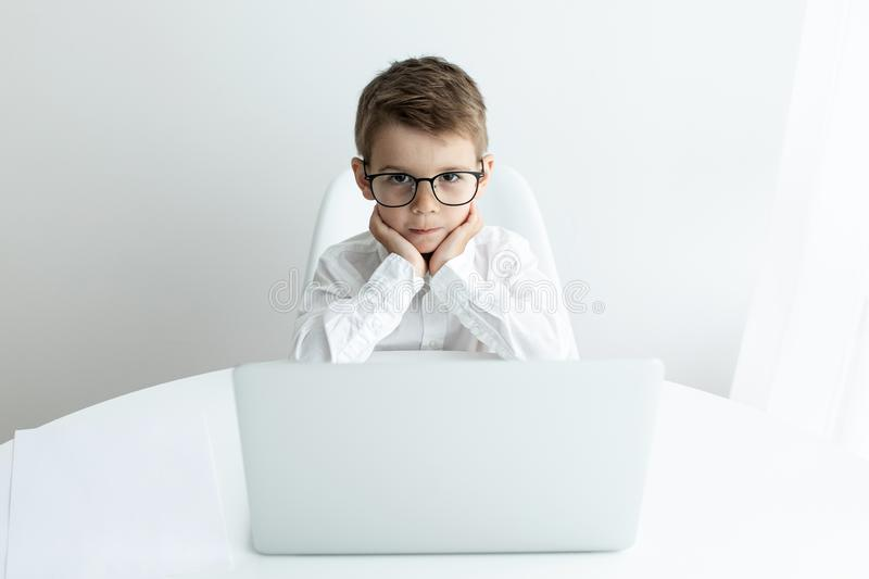 Cute little boy using laptop while doing homework against white background stock images