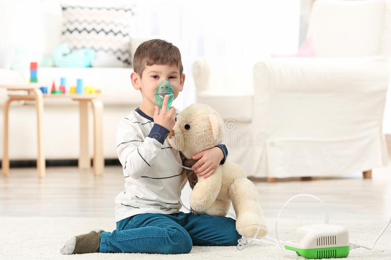 Cute little boy using nebulizer at home. Allergy concept royalty free stock photography