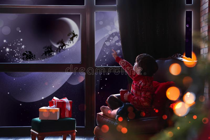 Cute little boy waiting for Santa Claus near window. Christmas holiday stock images