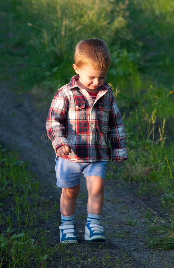 Download Cute Little Boy Walking In The Nature Stock Photo - Image of grass, path: 25061878