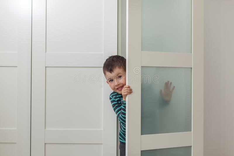 Cute little boy in wardrobe at home. Peeking, hiding, playing stock photos